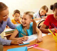 Teacher helping her school pupil in elementary school